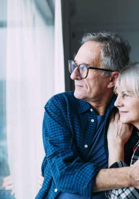 elderly couple looking out window